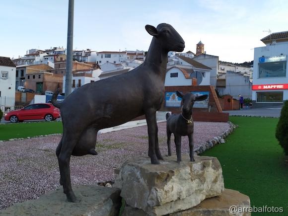 Monumento a la cabra malagueña y Fuente de los cuatro caños de Casabermeja con la Torre de la Iglesia del Socorro